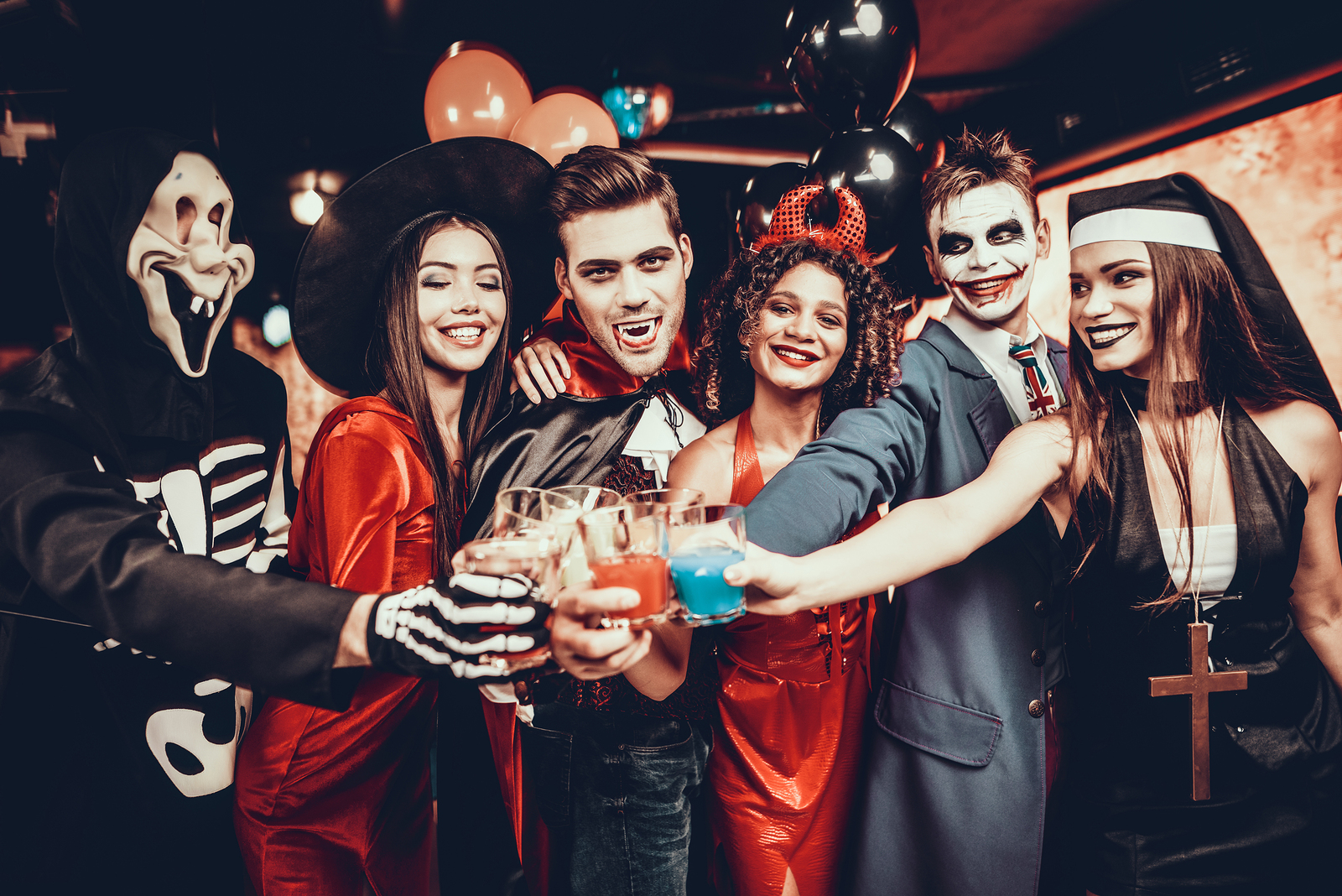 Friends In Halloween Costumes Drinking Cocktails. Group Of Young